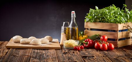 Panorama banner with fresh pizza ingredients, grated cheese, olive oil and mounds of individual portions of dough on a cutting board on a rustic kitchen table over a dark background with copy space