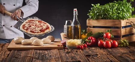 Chef in a pizzeria preparing an Italian pizza holding a paddle with a pastry base, tomato and cheese behind a rustic table with fresh ingredients and raw dough in a panorama banner