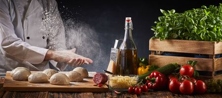 Chef clapping his floured hands creating a cloud of flour in the air as he prepares dough portions for pizzas on a table with fresh assorted ingredients in a panorama banner