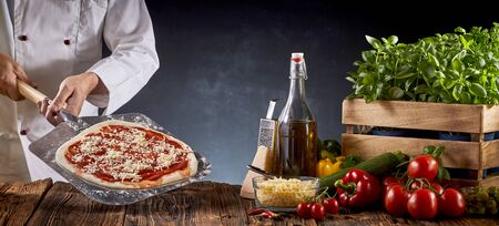 Chef making a traditional Margherita pizza holding a paddle with pie crust covered in tomato paste and cheese over a table with assorted fresh ingredients in a panorama banner