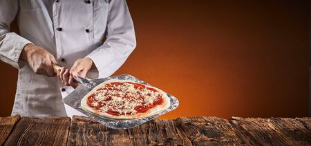 Chef in a pizzeria preparing an Italian pizza holding a crusty base with tomato paste and grated cheese on a metal paddle against a rustic table over a brown background with copy space in a wide angle panorama with glow of the oven fire