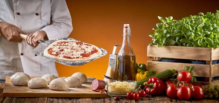 Cook preparing an Italian pizza in a restaurant holding a paddle with pastry base behind a rustic table with assorted fresh ingredients and portions of dough in a panorama banner