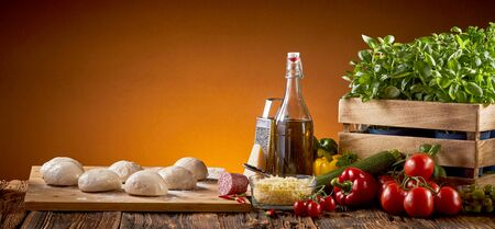 Fresh pizza ingredients with uncooked dough in individual portions on a rustic table over a brown background with copy space in a wide angle panorama Stock Photo