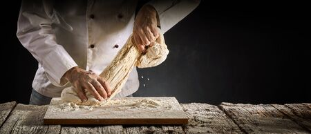 Baker or chef stretching a portion of raw dough as he works on it during preparation for cooking in a rustic panorama banner with copy space