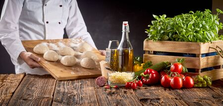 Chef in a pizzeria preparing Italian pizzas carrying a board with portions of raw dough to a rustic table with fresh ingredients in a panorama banner