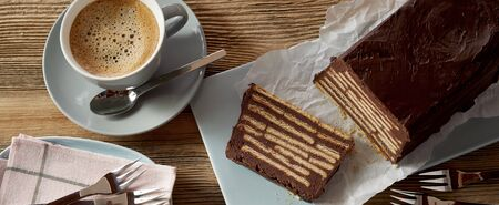 Overhead view of chocolate iced biscuit cake with one slice cut and a blue ceramic cup of creamy coffee