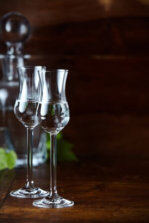Two tulip glasses of grappa on high legs on dark background with decanter and vertical copy space