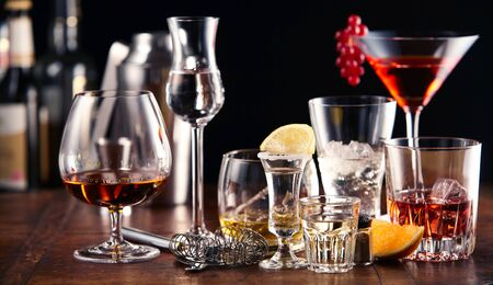 Large assortment of alcoholic beverages and cocktails served in appropriate glasses standing on a wooden bar counter Banco de Imagens