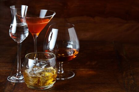 Nightlife or party concept with alcoholic beverages including cognac, whisky, liqueur and a martini arranged to the side with copy space on a wooden bar counter 免版税图像