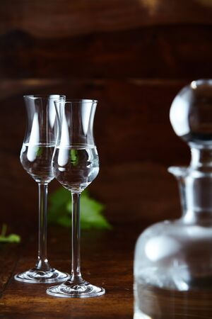 Two elegant tulip glasses of grappa and glass decanter blurred in foreground