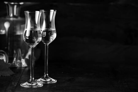 Two elegant grappa glasses and decanter in dark background, viewed from the side with copy space. Black and white contrast still life