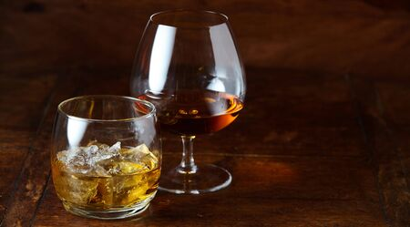 Whisky on the rocks and cognac in a snifter standing on a wooden bar counter at night with copy space 写真素材