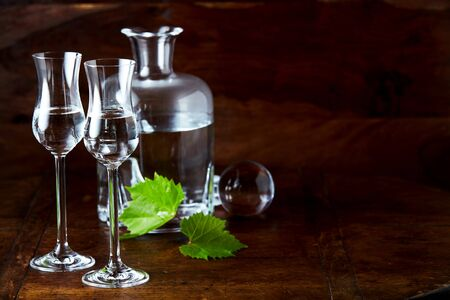 Grappa still life with two filled glasses, open decanter and green grape leaves. Copy space on dark wooden lacquered table background Imagens