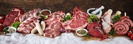 Große Auswahl an erstklassigem Rohfleisch für ein Wintergrillen im Panorama mit Schwein, Rind, Huhn, Steak und Würstchen in Folge auf Schnee mit frischen Kräutern und Gewürzen geeignet für Metzgerei-Werbung