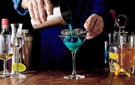 Bartender preparing a blue Curacao cocktail in a martini glass at a bar counter with an assortment of alcoholic beverages