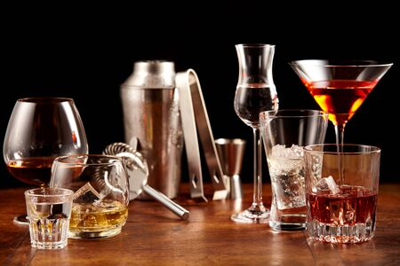 Assorted alcoholic beverages and bar utensils arranged as a still life on a wooden bar counter in a close up view conceptual of nightlife and entertaining