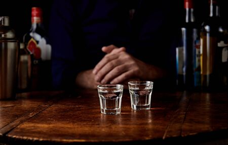 Man seated at a bar counter with two shots of vodka or schnapps in front of him in a close up view of his hands in the shadows conceptual of an addiction or alcoholism