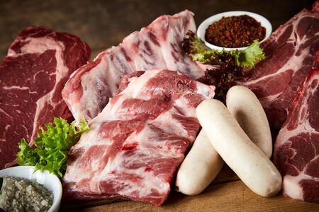 Raw spare ribs and pork or veal sausage displayed with assorted cuts of beef steak ready for a barbecue suitable for butchery advertising