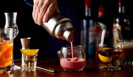 Bartender pouring a fruit cocktail from a shaker into a glass with assorted other alcoholic beverages on a bar counter in a close up view on his hand in shadowy light