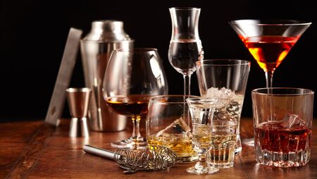 Bar utensils with an assortment of alcoholic drinks served in elegant glasses on a wooden counter in a nightclub or pub in a panorama banner 写真素材