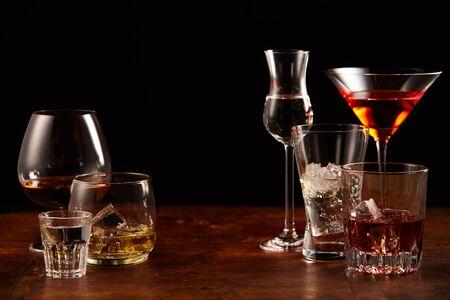 Una variedad de cócteles y bebidas alcohólicas servidos en vasos elegantes y mostrados en una barra de bar con espacio de copia central sobre negro Foto de archivo