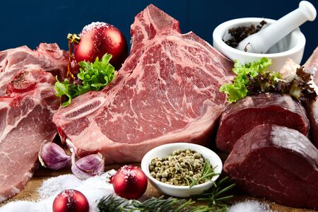 Raw meat, green salad and spices, combined with Christmas decorations in close-up winter holidays cooking ingredients concept