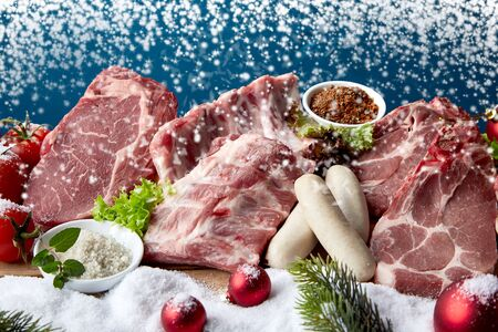 Raw meat pieces and uncooked sausages layout with snow and Christmas decorations, combined in winter holidays cooking ingredients concept