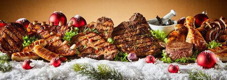 Variety of grilled meat in winter holiday banner concept with snow, Christmas decorations and pine trees, against light brown background