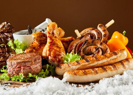 Delicious spicy grilled meat for a winter BBQ with a close up of a medallion of fillet steak, pork and beef sausage and chicken legs on a bed of fresh white snow