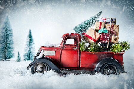 Festive red vintage truck laden with Christmas gifts and pine tree for decorating driving through a winter snow storm in a greeting card design with copy space