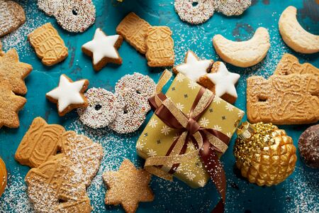 Festive Christmas food and baking background with assorted traditional freshly baked cookies surrounding a gold wrapped gift