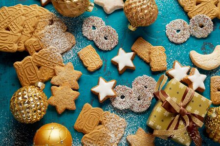 Christmas cookie or biscuit background with assorted shapes, including traditional speculaas, on a blue background with festive ornaments and gift 写真素材