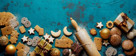 Christmas baking holiday banner or panorama with a variety of festive Xmas cookies, rolling pin, gifts and decorations on a cool toned blue background with copy space