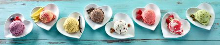 Rustic panorama banner of different ice cream flavors in scoops on individual heart shaped dishes with fresh ingredients on blue wood