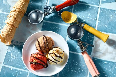 Serving of different flavored ice cream with three scoops and cornets or wafer cones on blue tiled
