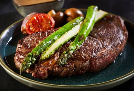 Thick juicy beef steak with fresh green green asparagus spears, tomato and mushrooms in close up on a plate with focus to the asparagus