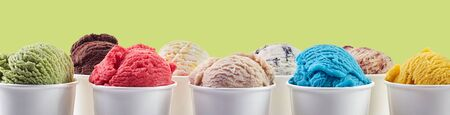 Large assortment of summer ice cream desserts in different flavors served in takeaway tubs over yellow in a wide panorama banner or header