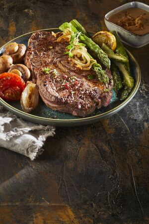 Serving of grilled beef steak and green asparagus spears with roasted tomato, mushrooms and onion on a wooden table with foreground copy space in vertical format Standard-Bild