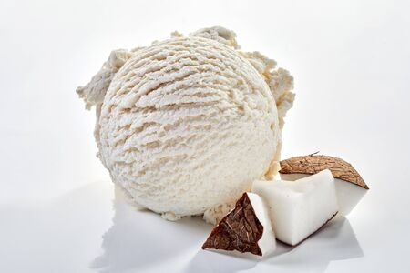Scoop of ice cream with coconut pulp in close-up on white
