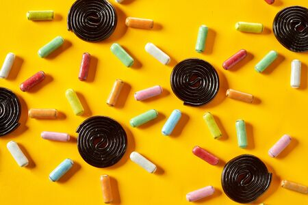 Background pattern of candy suns with spiral coiled liquorice centres and sugar-coated colorful rays on a tropical yellow background