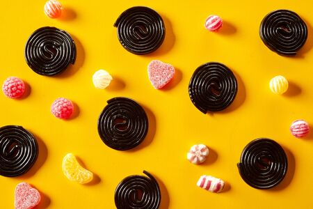 Spiral liquorice coils with fruity jub jub candy between scattered on a yellow background in a decorative pattern from overhead