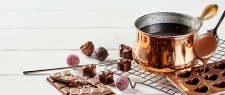 Making heart shaped Valentines chocolate bonbons pouring melted chocolate into moulds from a copper pot on a wire kitchen rack in a panorama banner