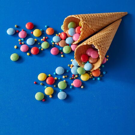 Rainbow colored sugar-coated chocolate candy and sprinkles spilling from two wafer cornets or ice cream cones onto a blue background in square format