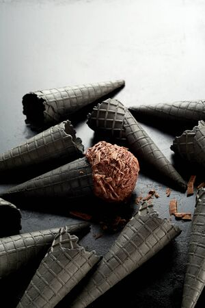 Random scatter of grey ice cream cones with one chocolate scoop covered in flakes in the center cornet over a gradient grey