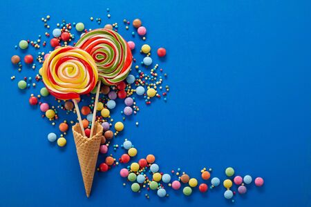 Artistic party background with colorful confectionery with sugar-coated chocolate sweets and sprinkles forming a trail around two spiral lollipops in ice cream cones on blue with copy space Foto de archivo