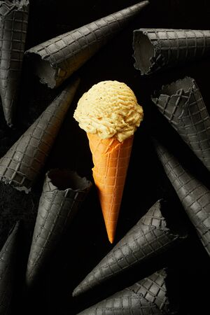 Single colored yellow scoop of ice cream in a cone amongst scattered empty monochromatic grey cornets over a black background in a conceptual food image