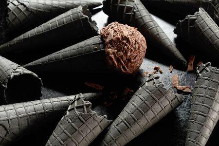 Black ice cream cones and chocolate scoop on dark surface. Studio shot in close-up