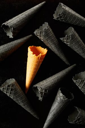 Single unique yellow ice cream cone amongst scattered grey cornets on a black full frame background in a conceptual food image