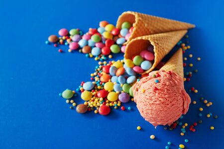 Colorful festive party background for Summer with berry ice cream in a wafer cone surrounded by sprinkles and two cornets spilling rainbow colored sugar-coated candies onto blue with copy space
