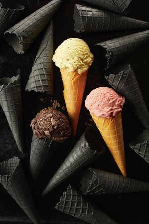 Strawberry, chocolate and vanilla ice cream in wafer cones amongst a monochrome background of grey cornets over a black background in a flat lay still life